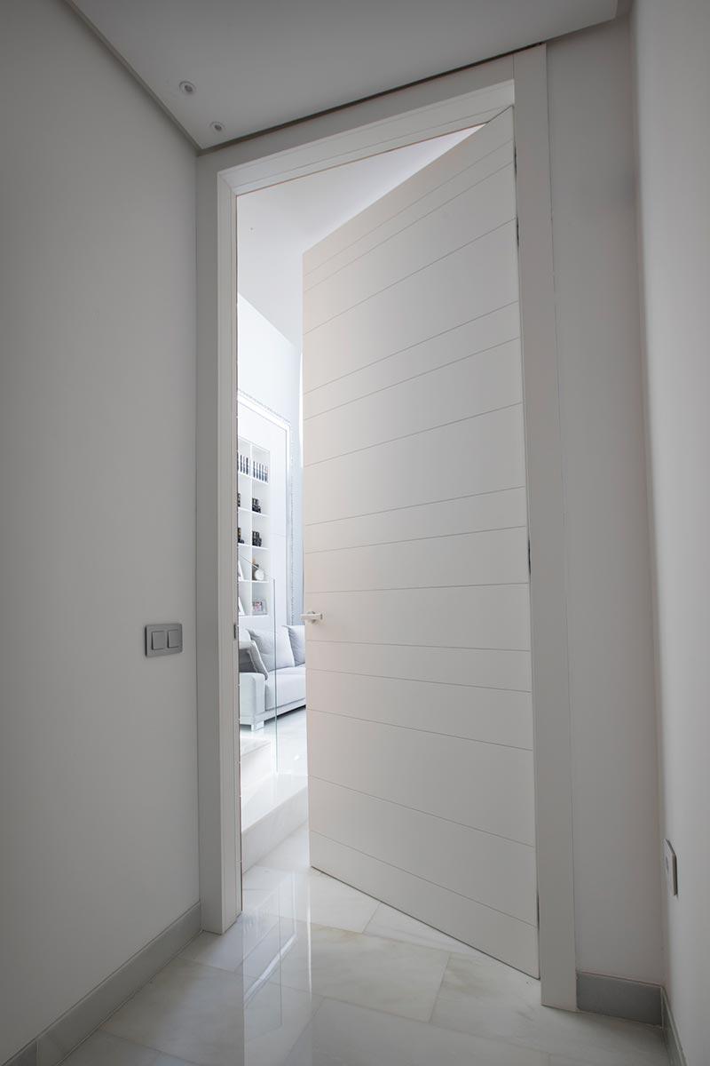 Puerta interior lacada de suelo a techo con ranuras horizontales alternas