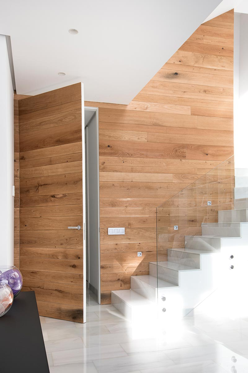 Pared escalera en casa unifamiliar con lamas de madera de roble