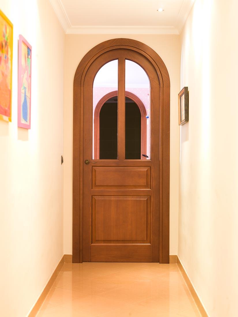 Puerta de madera pino melis con curva y cristalera