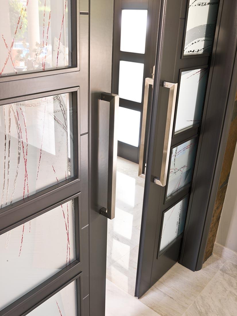 Puerta de doble cristal con manillones en acero inoxidable