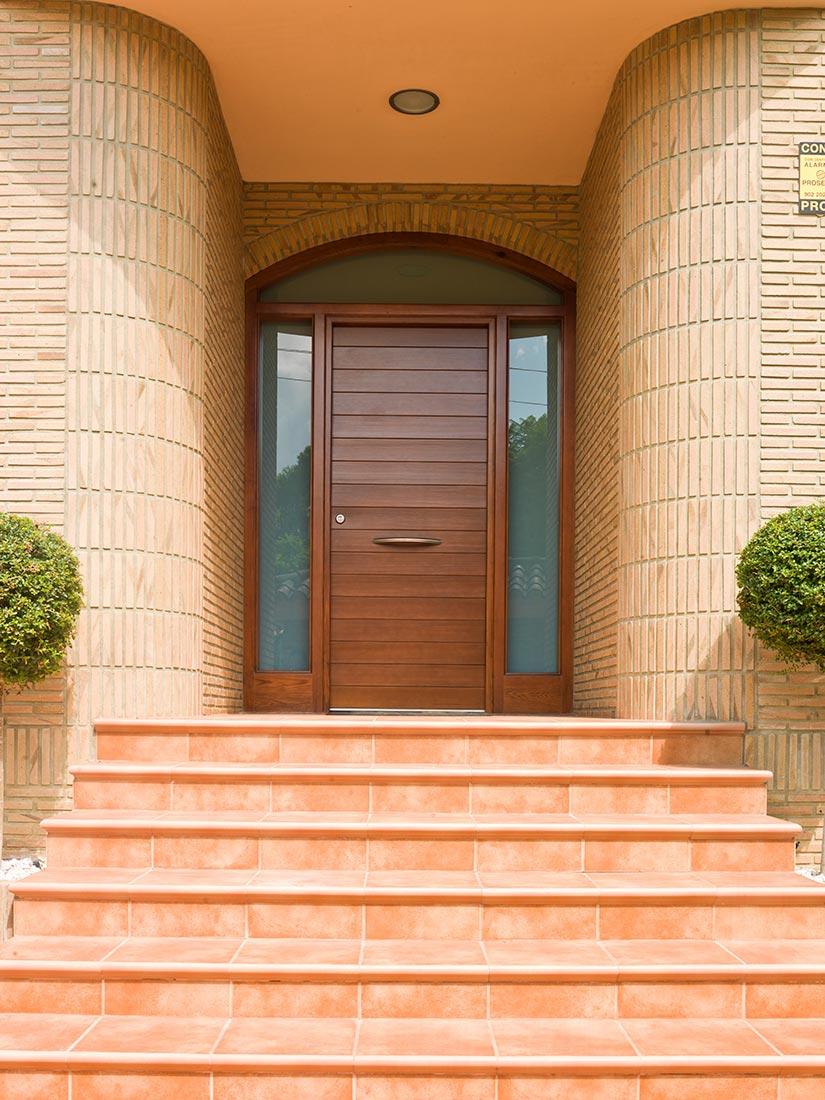 Puerta exterior de madera con curva y cristalera