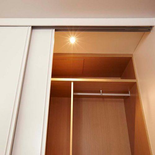 Interior de armario a medida con luz integrada en altillo