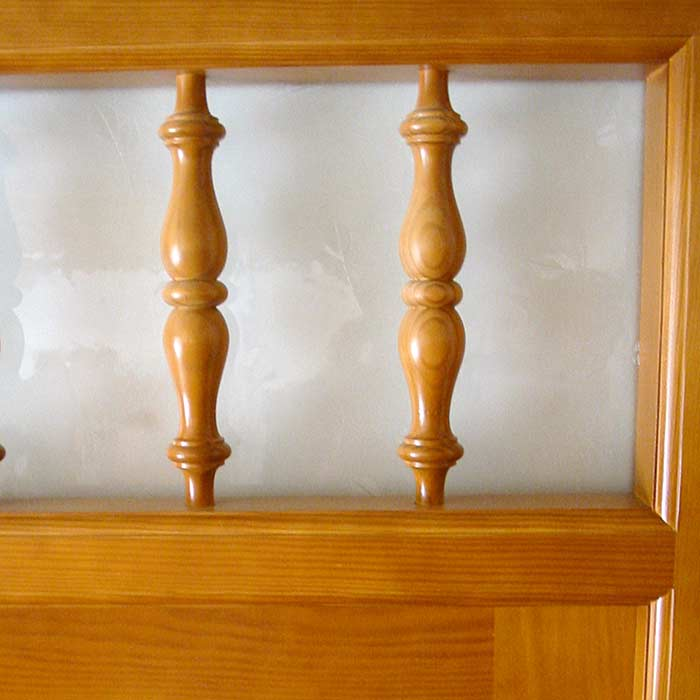 Detalle barrotes torneados en puerta exterior de madera