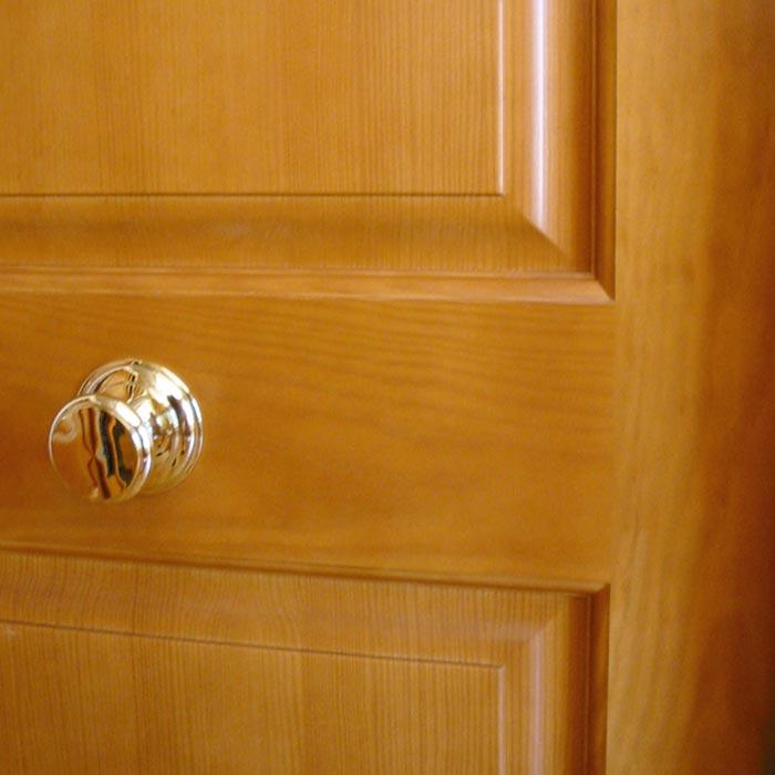 Pomo y detalle unión de tableros en puerta de madera