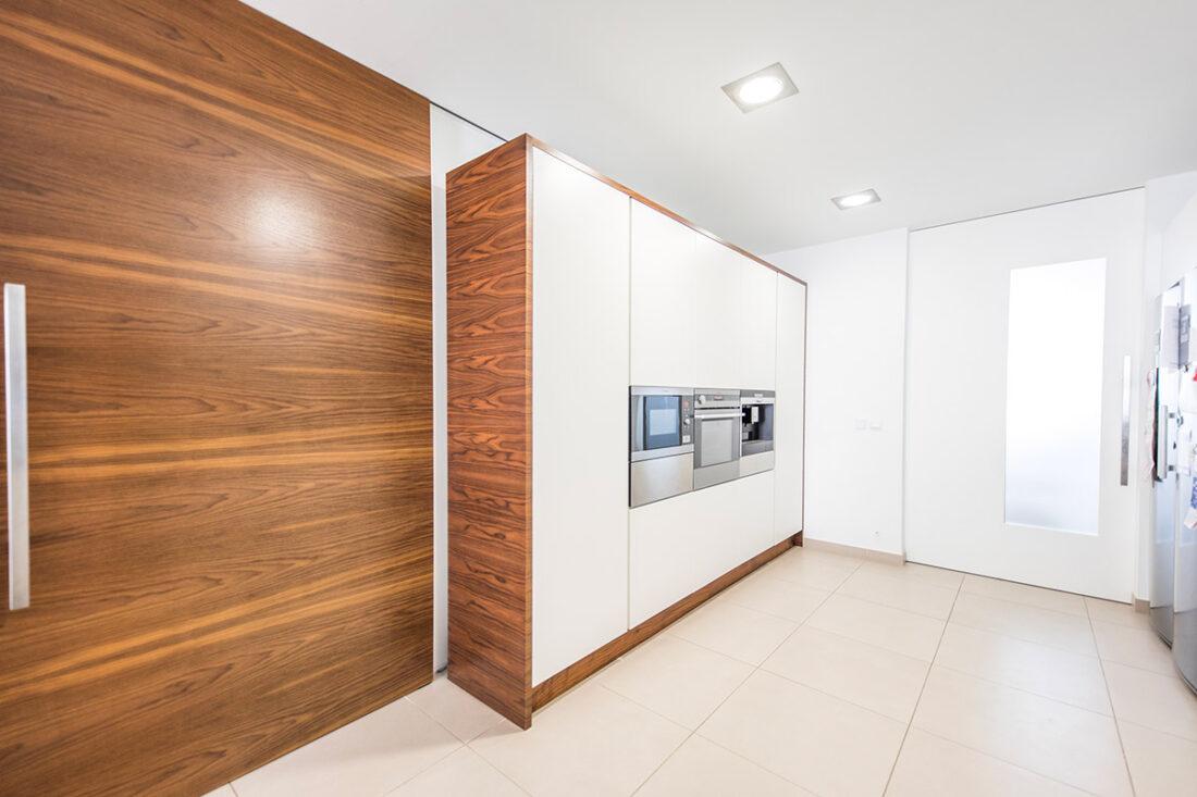 Armariada en madera para cocina junto a puerta corredera